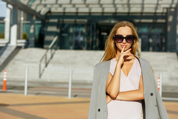 Fashionable blonde model in stylish glasses wearing pink dress and grey jacket. Space for text
