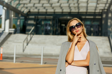 Amazing blonde lady in stylish glasses posing at the avenue in sunny day. Space for text