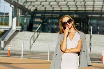 Charming blonde lady in stylish sunglasses posing at the street in sunny evening. Space for text