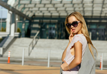 Attractive blonde lady in stylish sunglasses posing at the street in sunny evening. Space for text