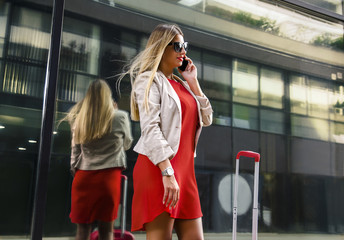 Attractive business woman in red dress and suitcase, talking on smartphone in front of modern building