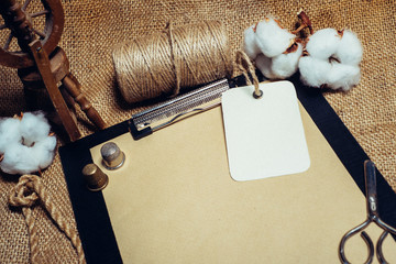 Close up rectangle tag on clipboard with vintage paper, beside cottons balls, rope and vintage spinning wheel. Mock up cotton template on sackcloth