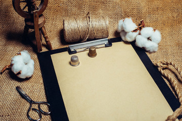 Close up clipboard with vintage paper, beside cottons balls, rope and spinning wheel. Mock up cotton template on sackcloth.