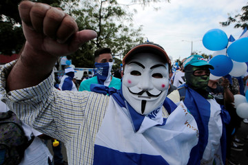 """A masked anti-government protester takes part in a march called """"March of the balloons"""" in Managua"""