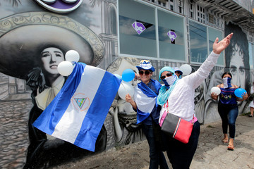 """Masked anti-government protesters pose for a photo during a march called """"March of the balloons"""" in Managua"""