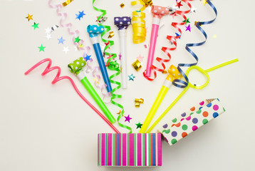 gift box with various party confetti, balloons, streamers, noisemakers and decoration on a green background. Colorful celebration background.