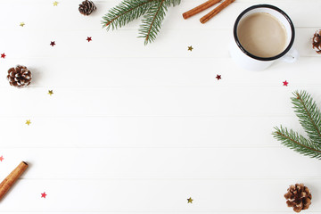 Christmas composition. Frame made of fir, spruce branches, pine cones, cinnamon sticks and glittering confetti stars on white wooden table background. Coffee in enamel mug. Flat lay, top view.