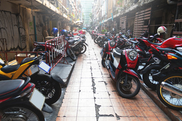 Parked scooters and motorcycles on the Bangkok city street