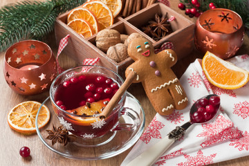 Mulled wine / Mulled wine winter hot drink in glass cup with cranberry, cinnamon, dried orange slices, anise star, spices, gingerbread cookies on wooden background