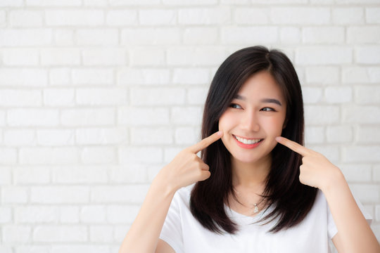 Portrait of beautiful young asian woman happiness standing finger touch cheek on gray cement texture grunge wall brick background, businesswoman is a smiling on concrete, business people concept.