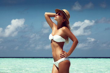 beautiful tanned woman on maldives island beach with turquoise sea on background.