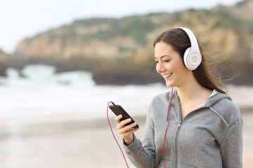 Teenage girl listening to music on the beach