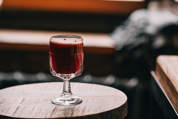 One glass of red mulled wine on wooden table. Dark food photography.