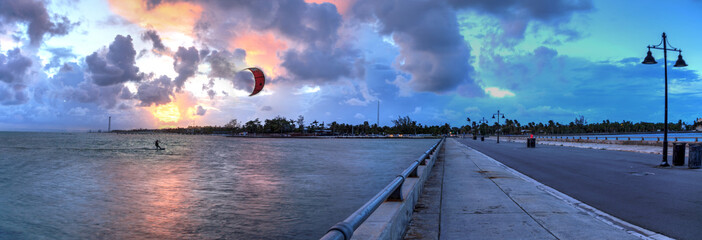 Kite surfer surfs alongside the Edward B. Knight Pier at sunset