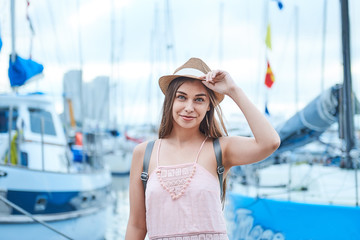 beautiful young woman travel girl on the background of a sea pier with boats and yachts, travel concept
