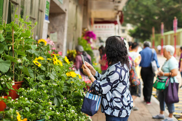 Woman taking photo with cellphone on flower market
