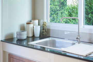 Clean kitchen sink with white ceramic dishware on counter top