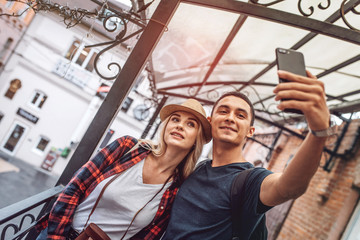 Modern embracing woman and man using phone and taking selfie on street in leisure