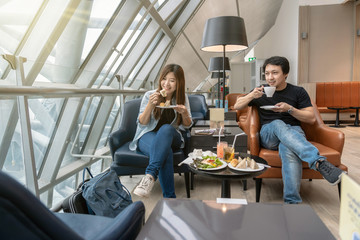 Fototapeta Asian couple sitting and eatting inn airport lounge when waiting the flight at modern international airport, travel and transportation concept obraz