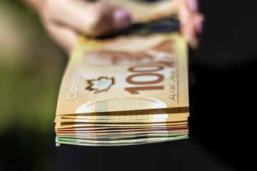 A Hand Holding a Bunch of Canadian Cash