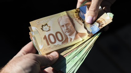 Hands Holding a Bunch of Canadian Cash