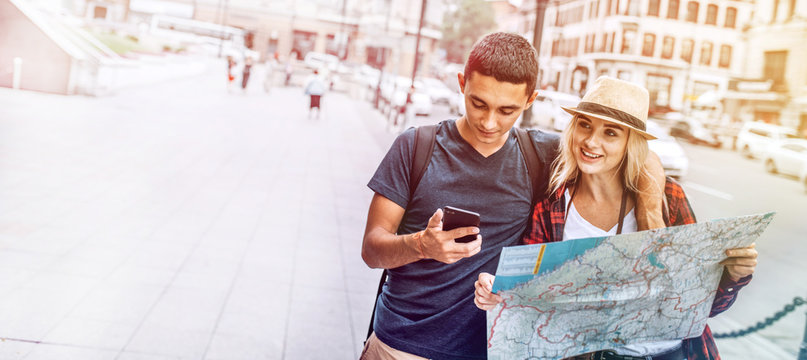 Casual young man and woman with map using phone on street exploring city while traveling