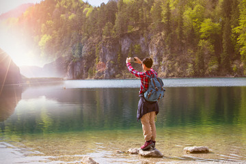 Back view of young man takes pictures by cellphone with a beautiful landscape and sun flare as lens glare