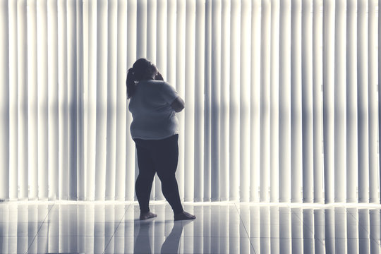 Pensive obese woman stands by the window