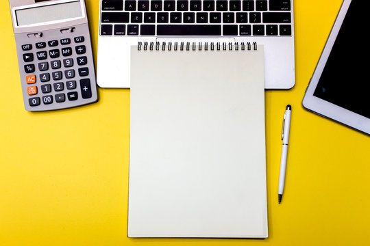 Yellow office desk table with  blank notebook, tablet and calculator. Top view