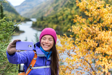 Happy asian hiker woman taking smartphone selfie at scenic viewpoint in nature fall mountain landscape outdoors. Girl hiking in Autumn forest park travel lifestyle. Girl holding phone.