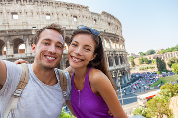 Wall Mural - Travel selfie couple taking photo with phone at colosseum famous landmark in Rome city. Europe Italy summer vacation young people smiling. Backpacking road trip.