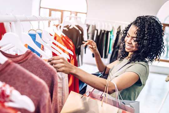 Happy black woman exploring rack with hangers in clothes store