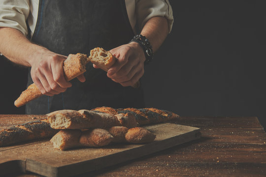 The baker keeps the baguette halves in his hands.