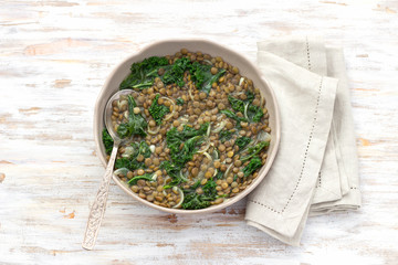 Stewed kale lentils with onions and garlic on a light background, selective focus. Delicious homemade healthy food