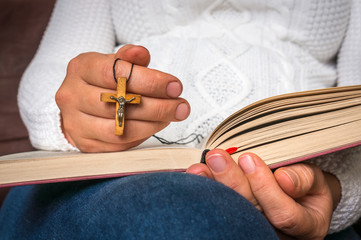 Christian woman with wooden cross reading a holy Bible