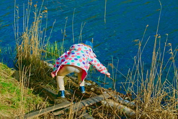 The child is playing on the bank of the road in the spring.