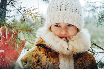 Portrait of a little girl in winter dress in a forest full of snow
