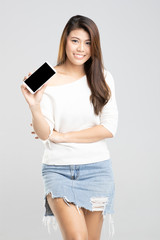 Studio shot of young beautiful Asian girl smile standing holder smartphone in hand isolated on white background