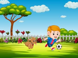 the boy playing soccer in the yard with his dog