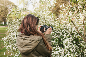 Portrait of a young woman photographer or tourist photographing nature in a park or garden. Professional occupation or hobby.