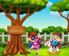 the boy uses the superhero costume and play with his friend near the big tree