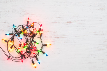 Wall Mural - Christmas lights bulb decoration on white wood. Merry Christmas and New Year holiday background. top view