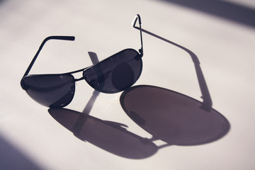Dark sunglasses lie on a white table, with long shadows, concept fashion