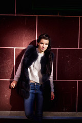 girl in a fur vest against a brick wall background