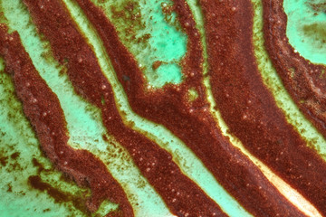 Green and brown abstract curve strips of melted ice cream. Summer background close-up.