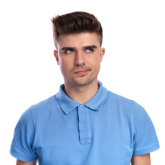 young casual man thinks and looks up to side