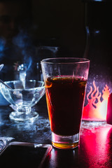 a glass of whiskey, or rum, or alcohol stands on a table on a dark background in the bar
