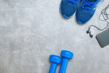 Sport concept background. Minimum equipment for workout, including sneakers, dumbbells and phone with headphones for listening music. Sport and healthy, backdrop for design with copy space.