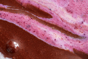 Abstractive structure of a mix colorful melted chocolate-berries ice cream close-up.