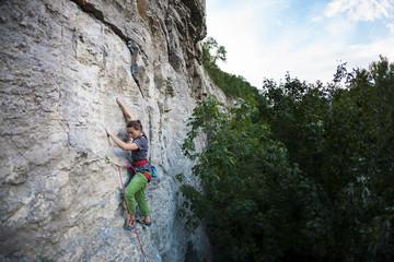 A strong girl climbs the rock.